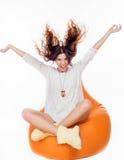 Härligt ung flickasammanträde på den orange kudden Royaltyfri Fotografi