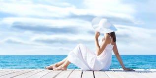 Härligt ung flickasammanträde på en pir i en vit klänning Sommar Royaltyfri Bild