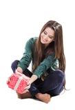 Härligt ung flickasammanträde på en vit bakgrund som rymmer en ask med en gåva leenden Arkivbild