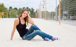 Härligt ung flickasammanträde på sandnexen till det netto för volleyboll av den soliga varma dagen Royaltyfri Fotografi