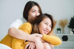 Härligt ungt asiatiskt lesbiskt lyckligt parsammanträde för kvinnor LGBT på säng som tillsammans kramar och hemma ler i sovrum royaltyfri fotografi