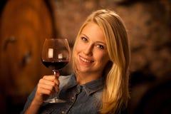 Härligt ungt blont kvinnaavsmakningrött vin i en vinkällare arkivbilder