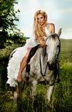 Ung blond brud som rider en häst i trendig klänning. Arkivfoton