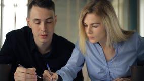 Härligt ungt blont kvinnasammanträde på en tabell med en man diskuterar arbetsinnehavhandtaget lager videofilmer