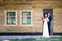 Härligt ungt gift par som poserar bredvid ett hus royaltyfri bild