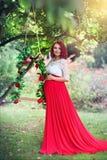 Härligt ungt gravid kvinnaanseende på i trädgården Arkivfoto