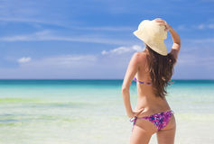 Härligt ungt kvinnaanseende på stranden som tycker om sunen Arkivfoto