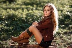 Härligt ungt kvinnasammanträde loggar på Royaltyfria Foton