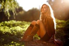 Härligt ungt kvinnasammanträde loggar på Royaltyfria Bilder