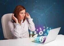 Härligt ungt kvinnasammanträde på skrivbordet och maskinskrivning på bärbar dator med Royaltyfria Foton