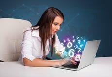 Härligt ungt kvinnasammanträde på skrivbordet och maskinskrivning på bärbar dator med Arkivbilder