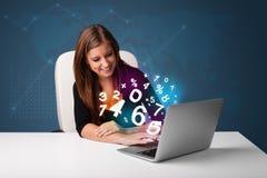 Härligt ungt kvinnasammanträde på skrivbordet och maskinskrivning på bärbar dator med Royaltyfri Bild