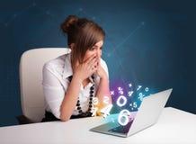 Härligt ungt kvinnasammanträde på skrivbordet och maskinskrivning på bärbar dator med Arkivfoto