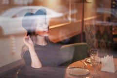 Härligt ungt le och lycklig kvinnablondin i hatt på restaurangtabellen till och med exponeringsglas Reflexioner royaltyfri fotografi