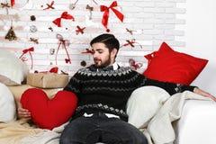 Härligt ungt ledset ensamt mansammanträde på sängen royaltyfria foton