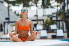 Härligt ungt sexigt kvinnasammanträde i Lotus poserar i en orange bikini under meditation Arkivbild
