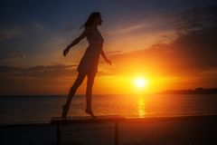 Härligt ungt spensligt kvinnaanseende på stranden på solnedgången, härlig kontur mot himlen arkivbilder