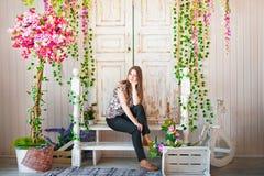 Härligt vårfotografi i den dekorerade inre En ung kvinna i blommor Arkivfoto