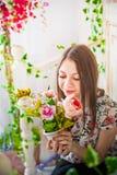 Härligt vårfotografi i den dekorerade inre En ung kvinna i blommor Royaltyfri Fotografi