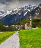 Härligt vårlandskap med kyrkan i de schweiziska fjällängarna Fotografering för Bildbyråer