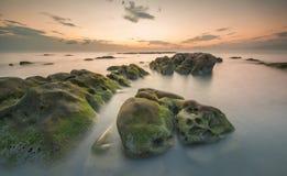Härligt vaggar bildande med grön mossa under solnedgång Arkivfoton