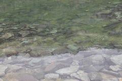 Härligt vatten av en bergsjö av vaggar mycket Arkivfoto