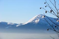 Härligt vinterlandskap med dolda berg för snö Royaltyfria Bilder