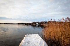 Härligt vinterlandskap vid havet med snö på en brygga och en lantlig horisont i bakgrunden royaltyfri bild