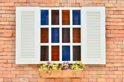 Härligt vitt träfönster med den färgrika blomman arkivfoton