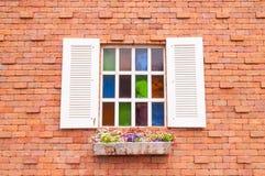 Härligt wood fönster med mång- färgexponeringsglas och tegelstenväggen Royaltyfri Foto