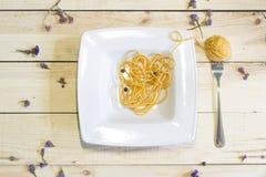 Härva på en gaffel som spagetti i plattan på en träbakgrund Royaltyfri Bild