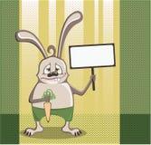 Häschen mit einer Karotte, die ein Zeichen hält Lizenzfreie Stockfotos