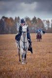 Häst-jakt med damtoalett i ridningvana royaltyfria bilder