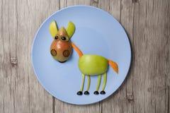 Häst som göras med äpplet och päronet på plattan och trätextur Arkivfoton