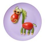 Häst som sammanställas av rå grönsaker på plattan Arkivbild