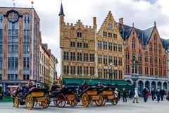 Hästdragen vagn med turister i Grote Markt, Brugge, Belgi Fotografering för Bildbyråer
