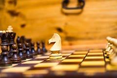 Hästen anfaller pantsätta i schack royaltyfri foto