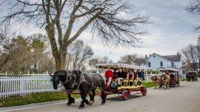Hästen drog vagnar transporterar passagerare på den Mackinac ön Arkivfoto