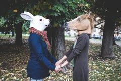 Hästen och kanin maskerar kvinnor i parkera royaltyfri foto