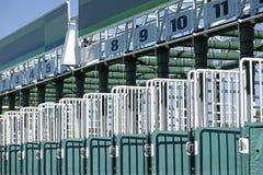 Hästkapplöpningstartportar med nummer på en solig dag arkivfoton