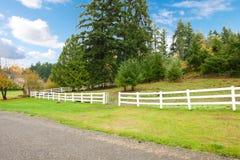 Hästlantgård med vita färgrika sidor för staket och för nedgång. royaltyfria foton