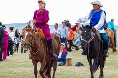 Hästryggkvinna & man i den traditionella dräkten, Nadaam hästkapplöpning royaltyfria bilder