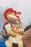 Hästryttare som bär guld- hjälmar med röda fjäderdräkter Royaltyfri Foto