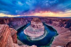 Hästskokrökning på Coloradofloden på solnedgången med dramatisk molnig himmel, Utah royaltyfri fotografi