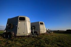 Hästtransportaskar som står på ett fält arkivfoto