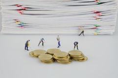 Häufen Sie Überlastungsdokument und Goldmünzen mit Miniaturleuten an stockbild