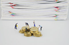 Häufen Sie Dokument und Goldmünzen mit Miniaturleuten an stockfoto