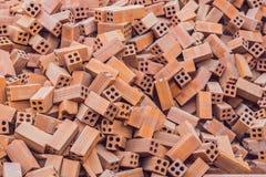 Häufen Sie Tapetenhintergrund des roten Backsteins, Abschluss oben des industriellen Maurers auf Baustelle an Lizenzfreie Stockbilder