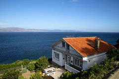 Häuschen auf dem Abhang durch das Meer Lizenzfreie Stockfotografie