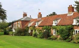 Häuschen auf einer englischen Dorf-Straße Stockfotos